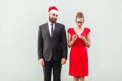 Proud man in christmas cap looking a gift. Frustrated woman hold stock images