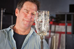 Holding Finished Glass Piece. Proud man holding finished glass piece with iron rod Royalty Free Stock Images