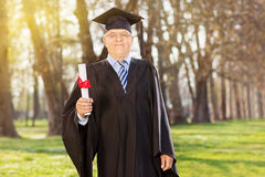 Proud mature student holding a diploma in park Stock Photography