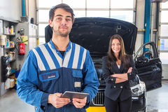 Proud mechanic, posing in front of a client with her car Stock Images