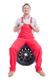 Proud mechanic sitting on car wheel tire Stock Images
