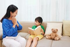 Proud mother. Mother is proud of her son reading a book stock image