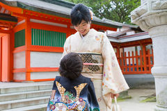 Proud 7-5-3 Mother with Son. A boy looks up at his proud and happy mother at a Japanese shrine; both are dressed in elegant kimonos; thiis boy of seven is here Royalty Free Stock Photo