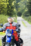 Proud of motorbike. A proud rider of a motorbike, country road background Stock Photography
