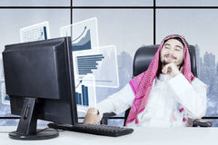 Proud muslim businessman looking profit graph. Proud muslim businessman looking at profit graph at virtual screen with winter background on the window Stock Image