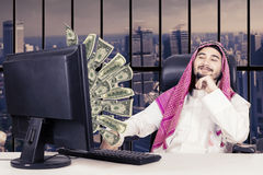 Proud muslim man looking money on monitor. Portrait of proud muslim man looking at money flying out of monitor while sitting on the chair Royalty Free Stock Photography
