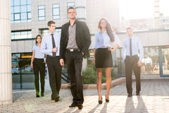 Proud Of My Team. Young businessman, elegantly dressed with his hand in his pocket, standing proudly with his team of young businesswomen and businessmen in Royalty Free Stock Images