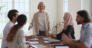 Mature leader unite happy multicultural team give high five together