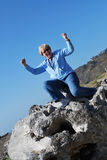 I Made It to the Top. Older lady sitting on top of a huge piece of gray driftwood hands raised up in the air and a joyful triumphed look on her face Stock Image