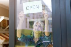 Senior woman holding open sign in organic produce shop stock photo