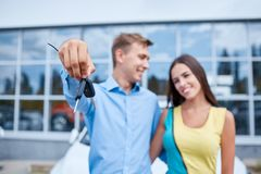 The family bought a new car in the showroom. The concept of buying a new car. Royalty Free Stock Photos