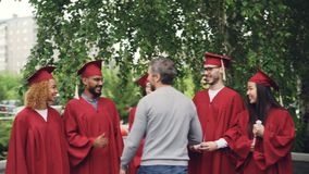 Proud parent is congratulating students on graduation day, shaking hands and hugging them on background of university. Campus, happy young people are talking stock video