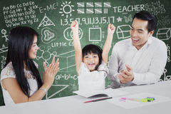 Proud parents giving applause on their child. Photo of two proud and happy parents giving applause on their daughter after finishing schoolwork stock photo