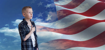 Proud Patriotic kid looks at American flag. Proud patriotic kid holding his hand on his heart and looks at american flag Stock Photos