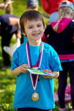 Proud preschool boy, holding prizes and medals Royalty Free Stock Image