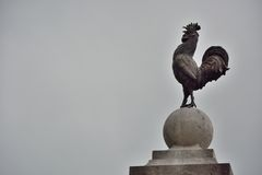 Proud rooster on a pedestal. Statue of a proud rooster on a pedestal surrounded by impressive dark morning  clouds in Vic-sur-sere,France Royalty Free Stock Photography