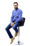 Proud and satisfied young man sitting on chair and looking at camera isolated on white Royalty Free Stock Image