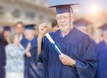 Proud Senior Adult Man In Cap and Gown At Outdoor Graduation Cer Stock Images