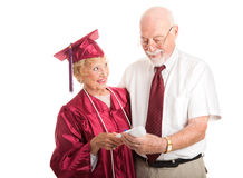 Proud Senior Graduate with Supportive Spouse. Senior women graduating from college, proudly shows her diploma to her husband.  Isolated on white Royalty Free Stock Photos