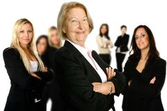 Proud senior leader with group. Confident mature female caucasian businesswoman leading a diverse team of female colleagues in the background. Concept of Stock Photo
