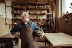 Proud senior potter in apron standing with ceramic bowl at workshop royalty free stock photo