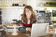 Proud shop owner. Shot of a smiling cafe owner standing by the counter and using laptop. Small business Royalty Free Stock Photography