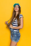 Proud Slim Girl. Beautiful young woman in dungarees and blue striped shirt and plastic sun visor. Three quarter length studio shot on yellow background Royalty Free Stock Photography
