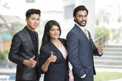 Proud smiling business people showing success sign Royalty Free Stock Photos
