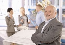 Proud smiling senior businessman with team royalty free stock images