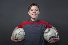 Proud, smiling teenage boy holding two soccer ball's Stock Photo