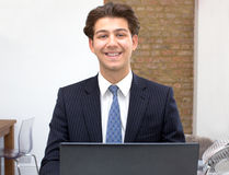Proud smiling young businessman at his desk Royalty Free Stock Photos