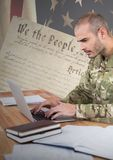 Proud soldier using a laptop with american flag background Royalty Free Stock Image