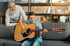 Grandfather watching his grandson play guitar Royalty Free Stock Image