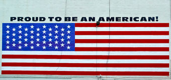 Proud to be an American. Detail American flag painted on a wall, with a very patriotic phrase Stock Images