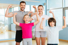 Proud to be strong and healthy. Happy sporty family showing their biceps and smiling while standing close to each other in sports club Royalty Free Stock Photography