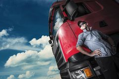 Proud Trucker and His Truck. Caucasian Trucker with Euro Semi Tractor Closeup Photo royalty free stock photography