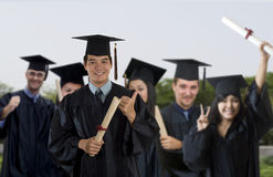 Proud University graduate. Young men wearing graduation cap and gown with classmates Royalty Free Stock Photos