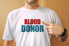 Proud volunteer blood donor wearing white t-shirt. Male person posing at camera stock images