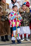 Proud of wearing his colorful ragged Kuker costume. PERNIK, BULGARIA - JANUARY 26, 2018: Young male participant in colorful rag Kuker costume leans on wooden Stock Photography