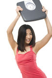 Proud of weightloss. A beautiful woman holding up a weight scale above her head Stock Photo
