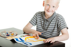Proud young boy artist doing finger painting Royalty Free Stock Photo