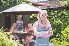 Proud young business owner standing in front of her cafe Royalty Free Stock Photo