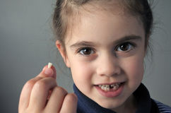 Proud young girl holds her first falling milk teeth Stock Photography