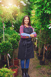 Proud young nursery owner standing in a greenhouse Royalty Free Stock Photo