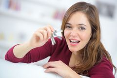 Proud young woman holding up set house keys. Proud young woman holding up a set of house keys Royalty Free Stock Images