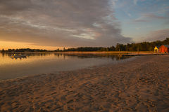 Prouts Neck Beach Sunset in Scarborough, Maine. Brilliant late summer sunset with boats, pier, and rustic boathouses at Prouts Neck Beach in Scarborough, Maine Stock Photos