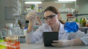 Prov för resultat för kontroll för ståendekvinnadoktor i laboratorium royaltyfri bild