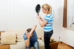 Prova arrabbiata della giovane donna colpita il suo marito con la pentola Immagine Stock Libera da Diritti