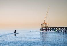 Prova del proprietario della barca per raggiungere la sua barca in spiaggia di Pasir Putih, situbondo Immagini Stock