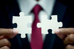 Prova dell'uomo d'affari per collegare in due pezzi del puzzle Fotografia Stock